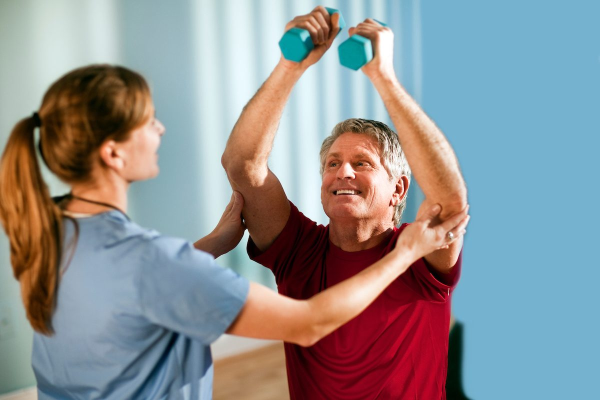 Middle-aged man lifts dumbbells with the assistance of a young physical therapist. Horizontal shot.